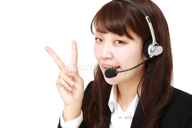 Giovane donna di affari giapponese della call center con gli insiemi capi fotografia stock libera da diritti