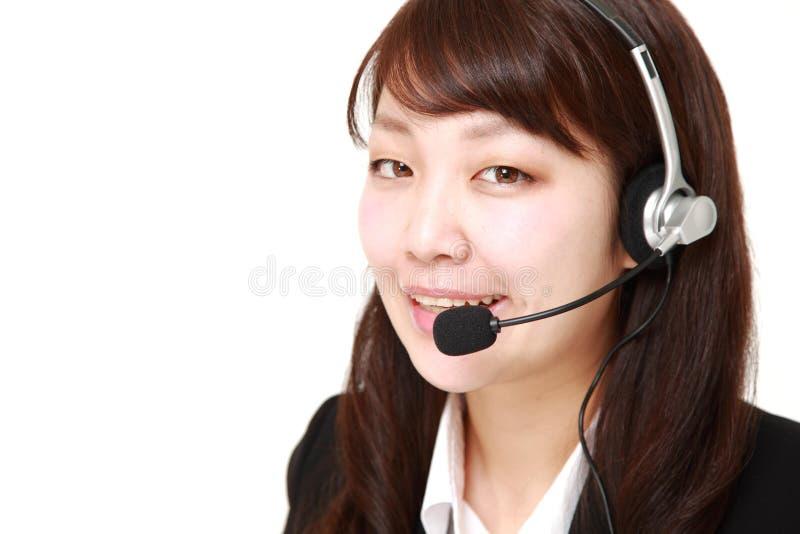 Giovane donna di affari giapponese della call center con gli insiemi capi fotografia stock