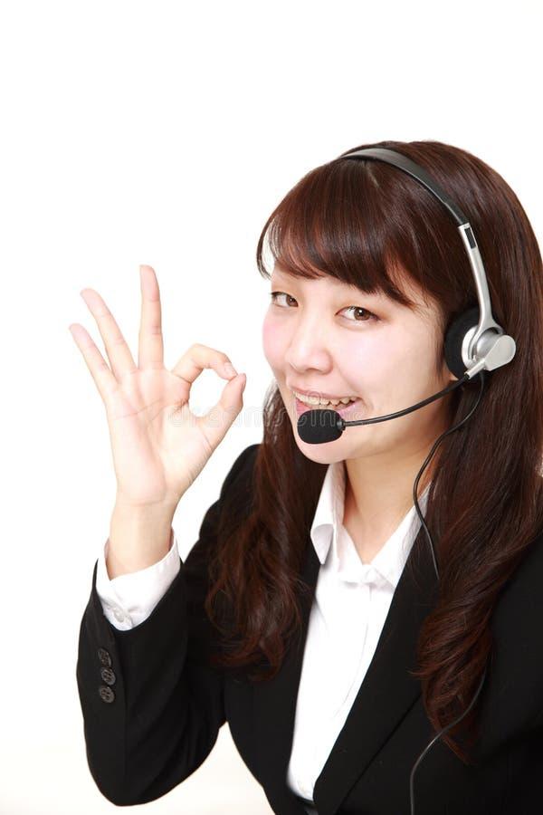 Giovane donna di affari giapponese della call center con gli insiemi capi fotografie stock libere da diritti