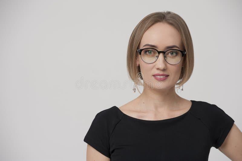 Giovane donna di affari incantante sorridente che indossa vestito convenzionale ed i vetri alla moda immagine stock
