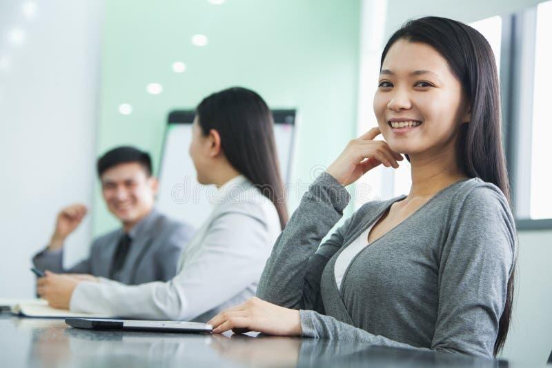 Giovane donna di affari Looking At Camera in una riunione fotografia stock