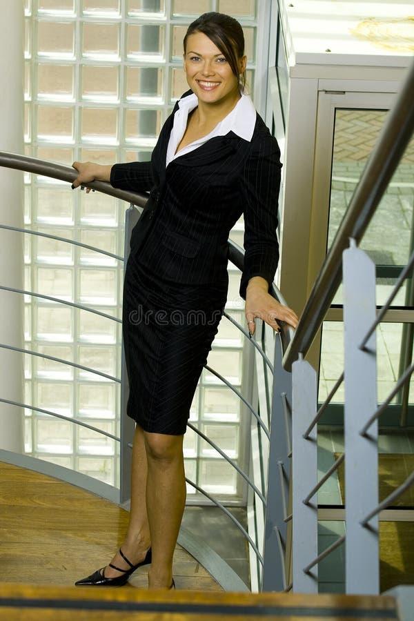 Giovane donna di affari matura che sta accanto ad una parete fotografia stock