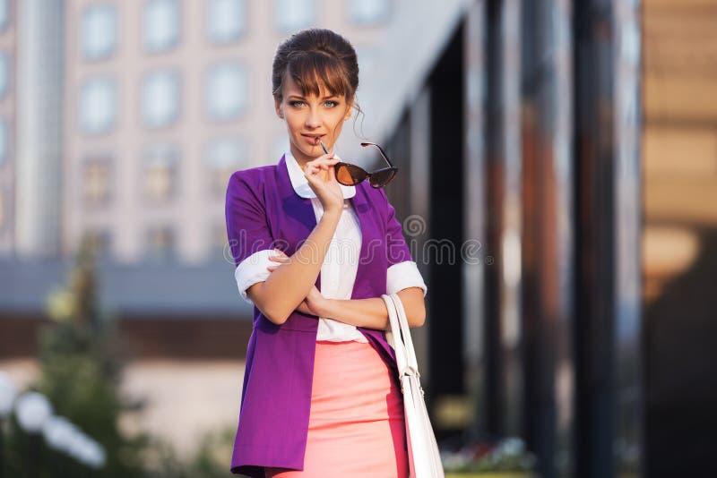 Giovane donna di affari di modo che porta giacca sportiva porpora che cammina in via della città immagini stock libere da diritti