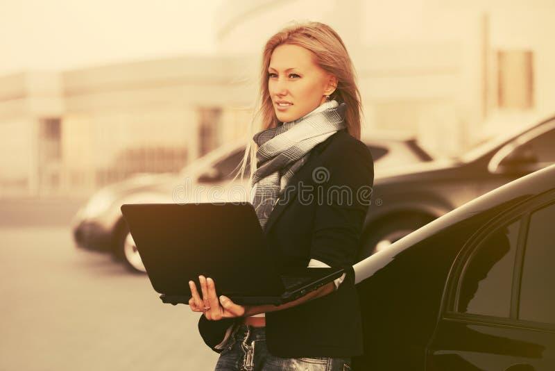 Giovane donna di affari di modo con il computer portatile accanto alla sua automobile su parcheggio fotografie stock libere da diritti
