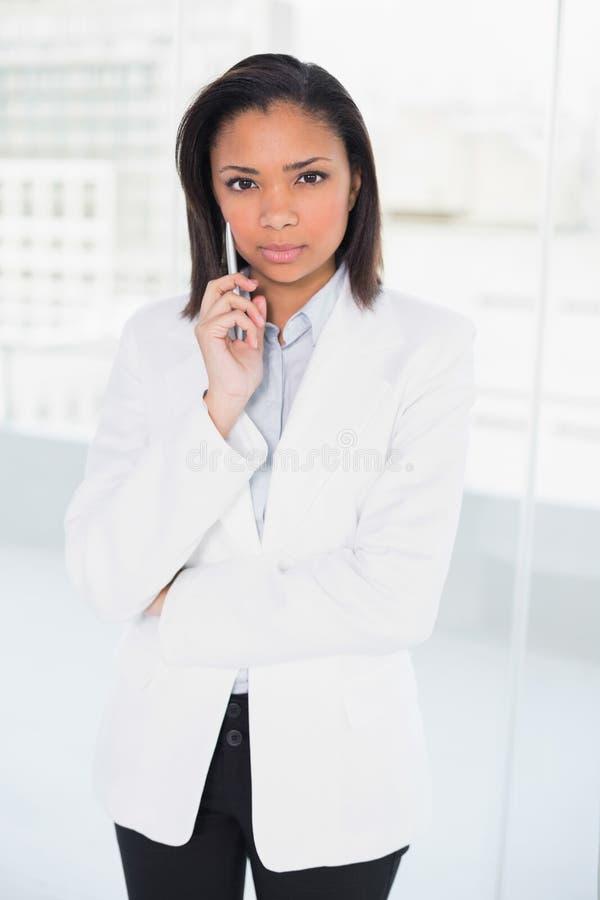 Giovane donna di affari mora adorabile che posa esaminando macchina fotografica immagine stock libera da diritti