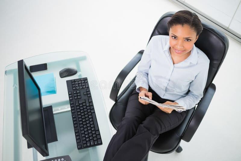 Giovane donna di affari mora contenta che legge una rivista fotografie stock libere da diritti