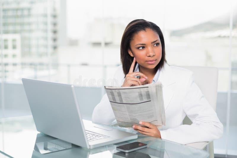 Giovane donna di affari mora pensierosa che legge un documento fotografia stock libera da diritti