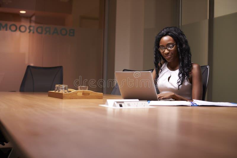 Giovane donna di affari nera che lavora tardi sul computer portatile in ufficio immagine stock libera da diritti