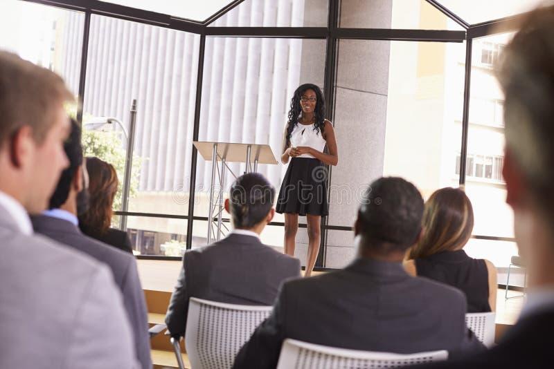 Giovane donna di affari nera che presenta seminario ad un pubblico fotografia stock libera da diritti