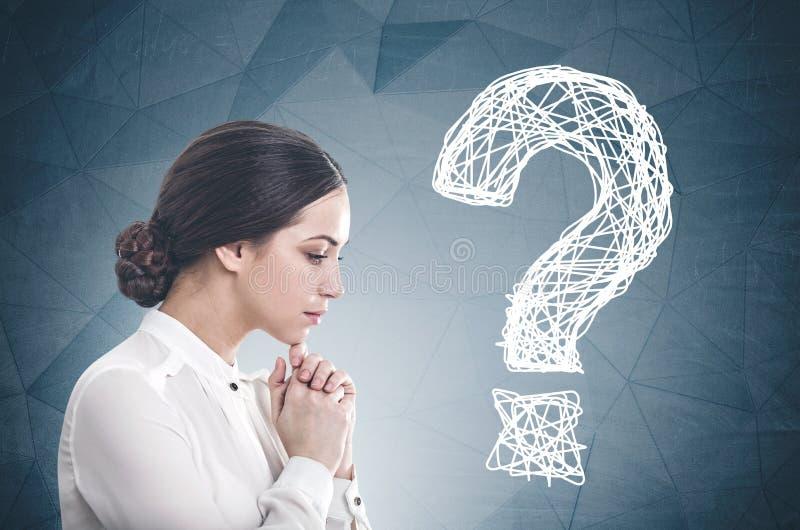 Giovane donna di affari pensierosa, punti interrogativi immagini stock