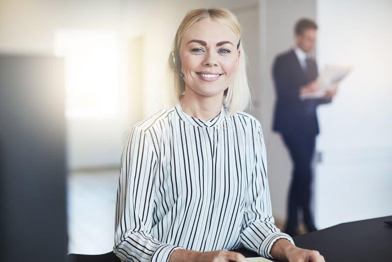 Giovane donna di affari sorridente che indossa una cuffia avricolare alla sua scrivania fotografia stock libera da diritti
