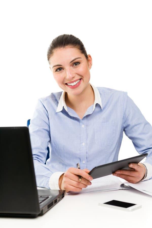 Giovane donna di affari sorridente che per mezzo della compressa sul suo scrittorio immagini stock