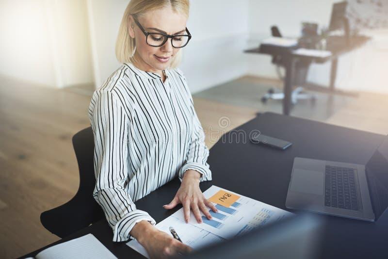 Giovane donna di affari sorridente che supera i documenti al suo ufficio d immagine stock