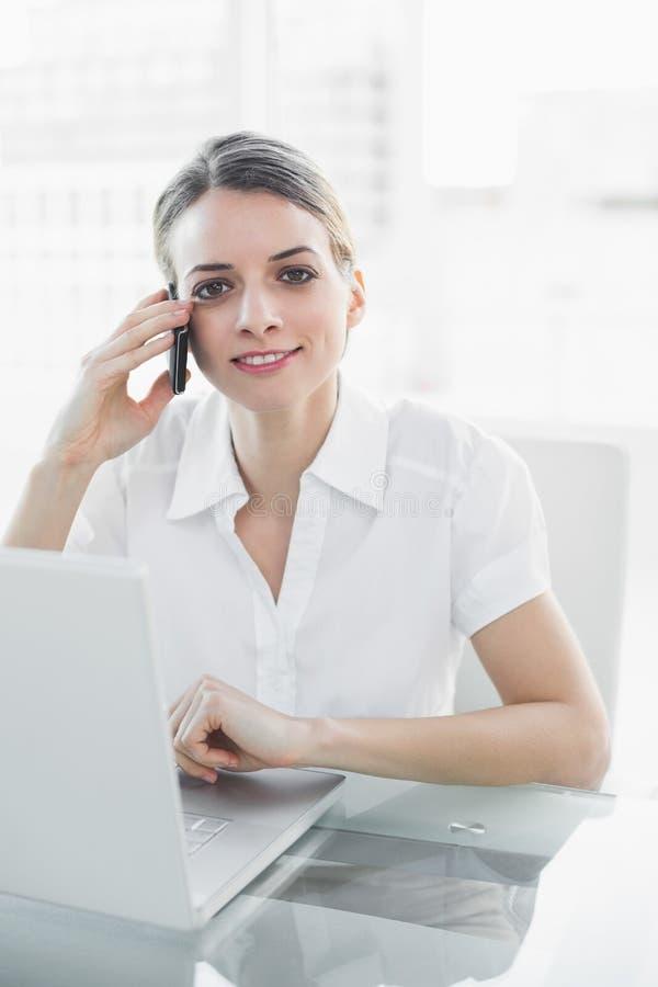 Giovane donna di affari sorridente che telefona con il suo smartphone che esamina macchina fotografica fotografia stock