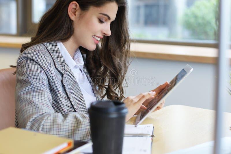 Giovane donna di affari sorridente in ufficio che lavora alla compressa digitale fotografia stock libera da diritti