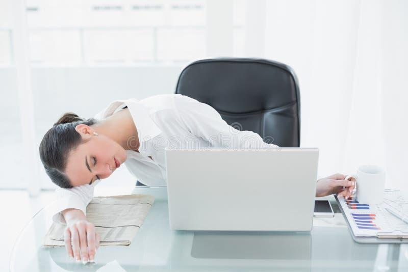 Giovane donna di affari stanca che riposa nell'ufficio immagini stock libere da diritti