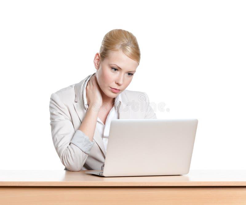 Giovane donna di affari stanca che si siede ad una scrivania con il computer portatile fotografie stock libere da diritti