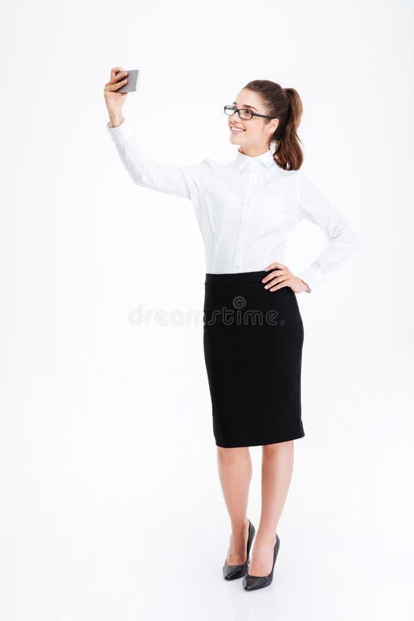 Giovane donna di affari sveglia allegra che prende selfie facendo uso del telefono cellulare fotografia stock