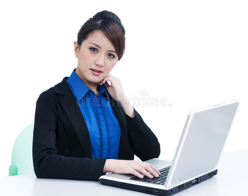 Giovane donna di affari sveglia che per mezzo del computer portatile immagini stock libere da diritti