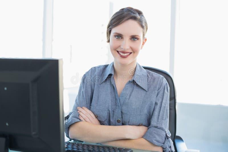 Giovane donna di affari sveglia che si siede al suo scrittorio con le armi attraversate fotografie stock