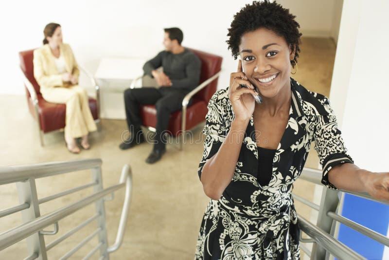 Giovane donna di affari Using Mobile Phone sulle scala immagini stock