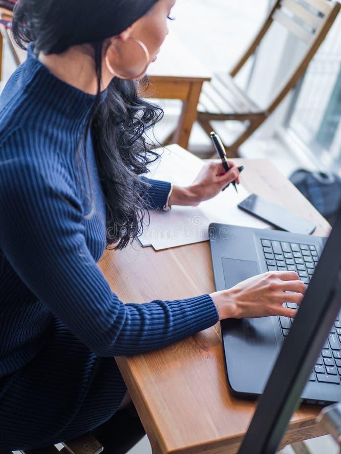 Giovane donna di affari in vestito grigio che si siede alla tavola in caffè e che scrive in taccuino Sulla tavola è il computer p fotografia stock libera da diritti