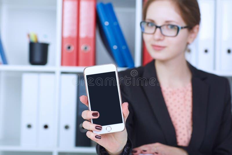 Giovane donna di affari in vetri che mostrano uno schermo in bianco dello smartphone Fuoco sullo smartphone fotografie stock