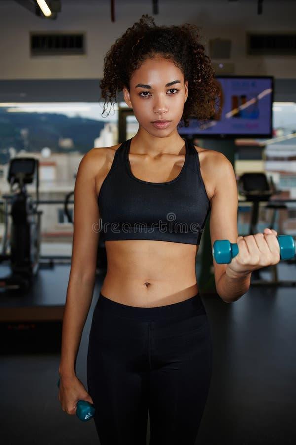 Giovane donna di afro che si esercita con i pesi liberi al centro di forma fisica fotografie stock
