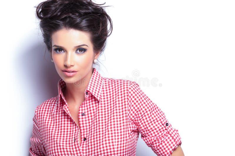 Giovane donna di bellezza in camicia rossa e nell'acconciatura piacevole fotografia stock