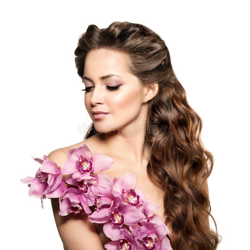 Giovane donna di bellezza, capelli ricci lunghi di lusso con il fiore dell'orchidea H fotografia stock libera da diritti