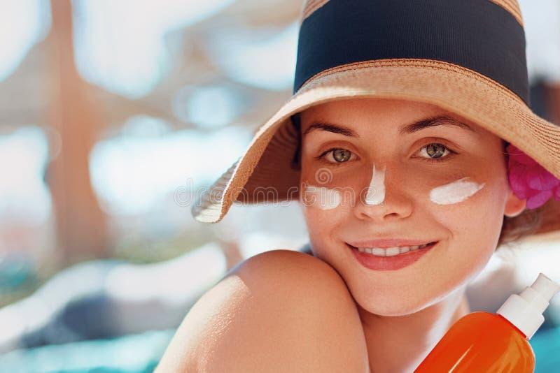 Giovane donna di bellezza con la crema del sole sul fronte che tiene la bottiglia della protezione solare sulla spiaggia fotografie stock libere da diritti