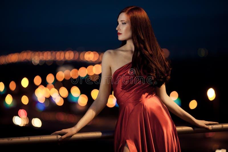 Giovane donna di bellezza in vestito rosso esterno immagine stock libera da diritti