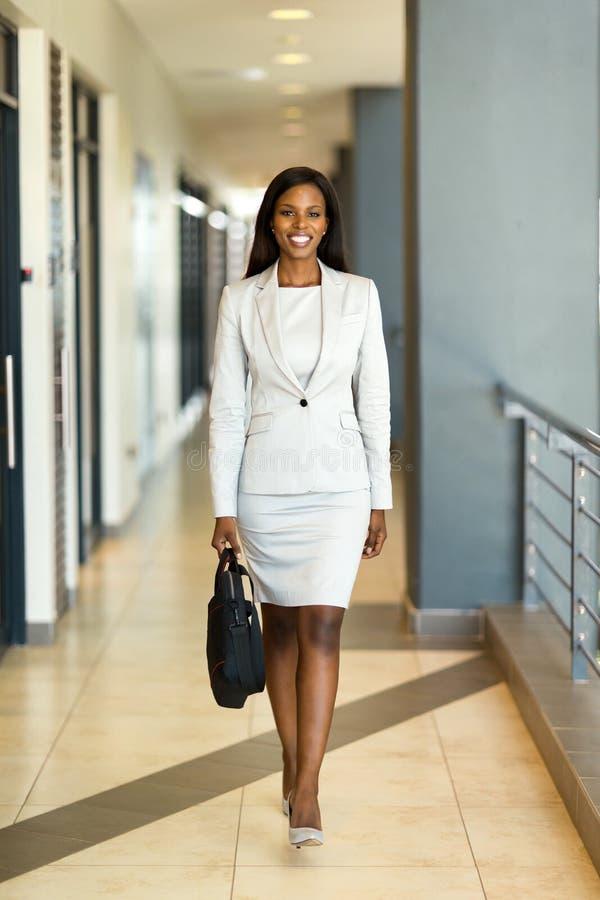 Giovane donna di carriera africana che cammina nell'edificio per uffici fotografie stock libere da diritti