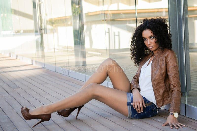Giovane donna di colore, acconciatura di afro, nel fondo urbano fotografie stock