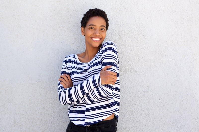 Giovane donna di colore allegra che sta contro la parete grigia immagine stock libera da diritti