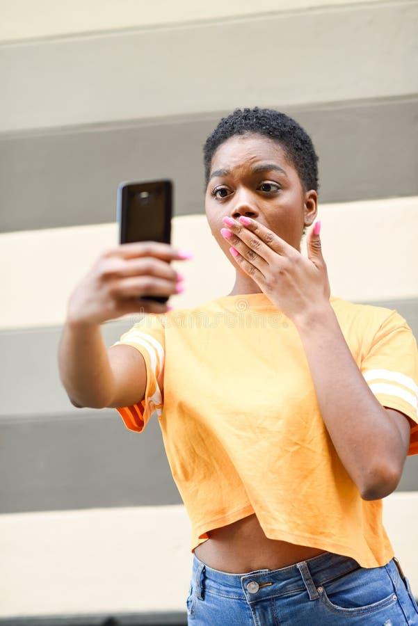 Giovane donna di colore che prende le fotografie del selfie con l'espressione divertente all'aperto fotografie stock libere da diritti
