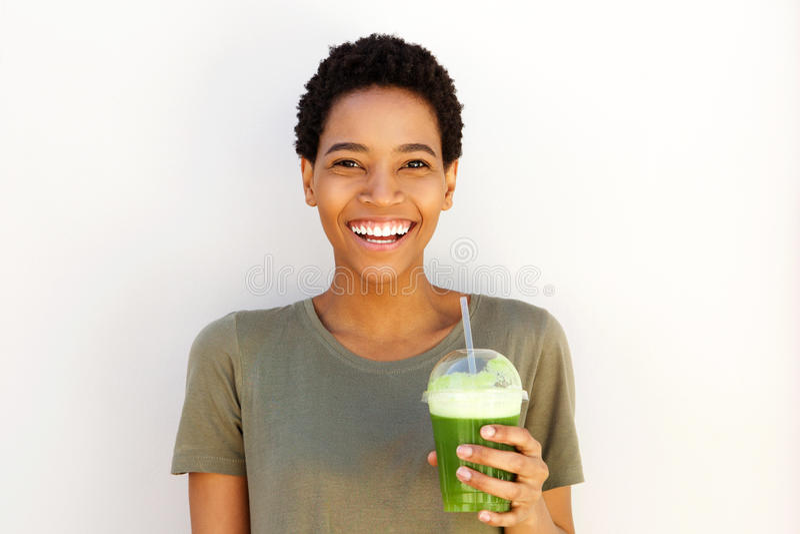 Giovane donna di colore che sorride con la tazza fresca del succo di frutta immagini stock