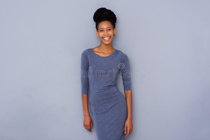 Giovane donna di colore che sorride contro la parete grigia immagine stock libera da diritti