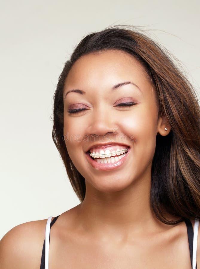 Giovane donna di colore con la grande parentesi graffa di sorriso fotografia stock