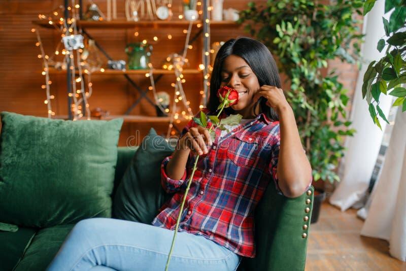 Giovane donna di colore con la rosa rossa che si siede sul sofà fotografia stock libera da diritti