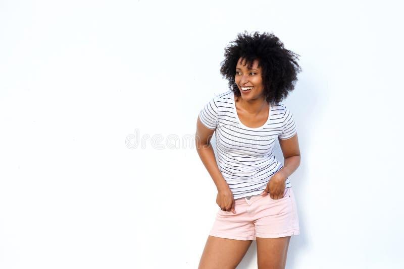 Giovane donna di colore d'avanguardia che distoglie lo sguardo e che sorride sul fondo bianco fotografia stock libera da diritti