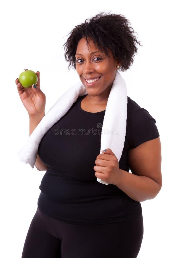 Giovane donna di colore di peso eccessivo che tiene una mela - gente africana immagine stock libera da diritti
