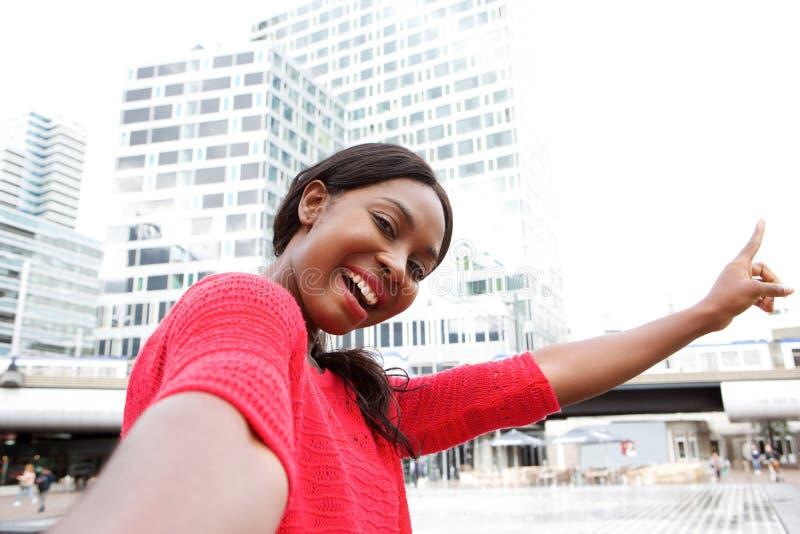 Giovane donna di colore felice che prende selfie nella città e che indica le costruzioni immagine stock libera da diritti