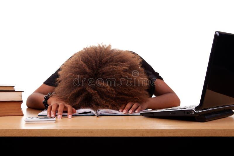 Giovane donna di colore sollecitata, sedentesi ad una tabella immagini stock