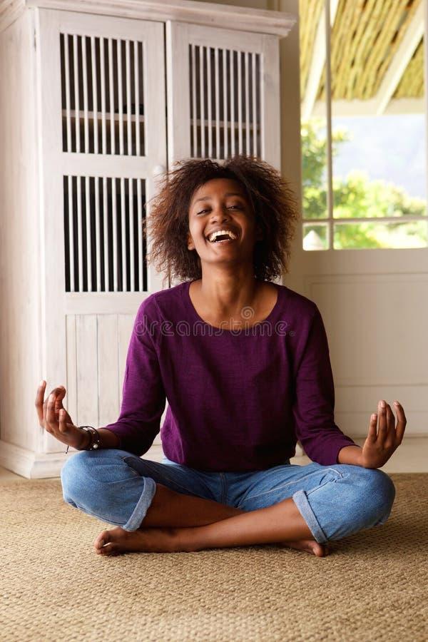 Giovane donna di colore sorridente che si siede sull'yoga di pratica del pavimento immagine stock