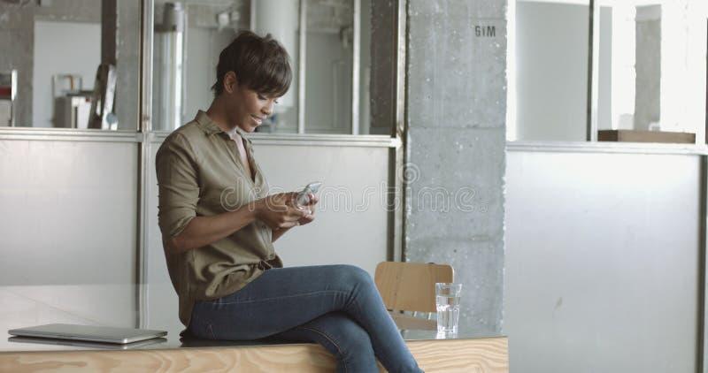 Giovane donna di colore sveglia nell'ufficio di stile del sottotetto immagini stock