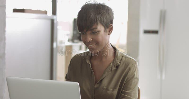 Giovane donna di colore sveglia nell'ufficio di stile del sottotetto immagine stock libera da diritti