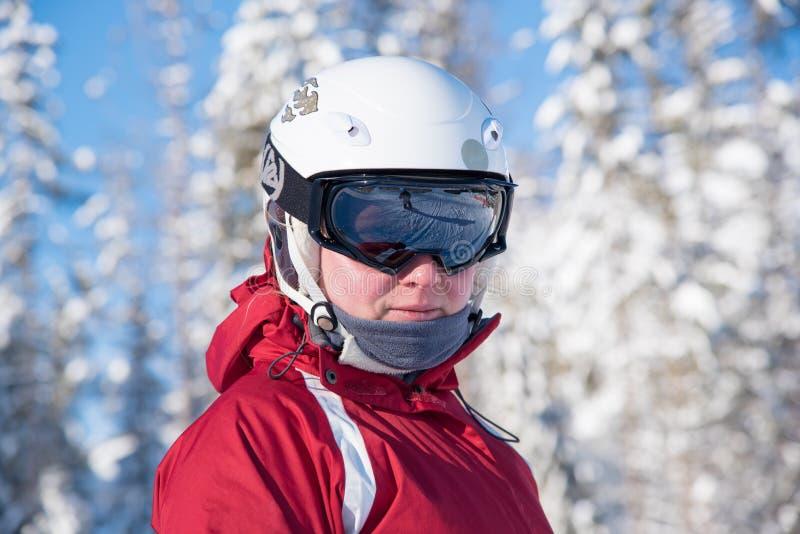 Giovane donna di corsa con gli sci con gli occhiali di protezione neri, il casco bianco ed il rivestimento rosso fotografia stock
