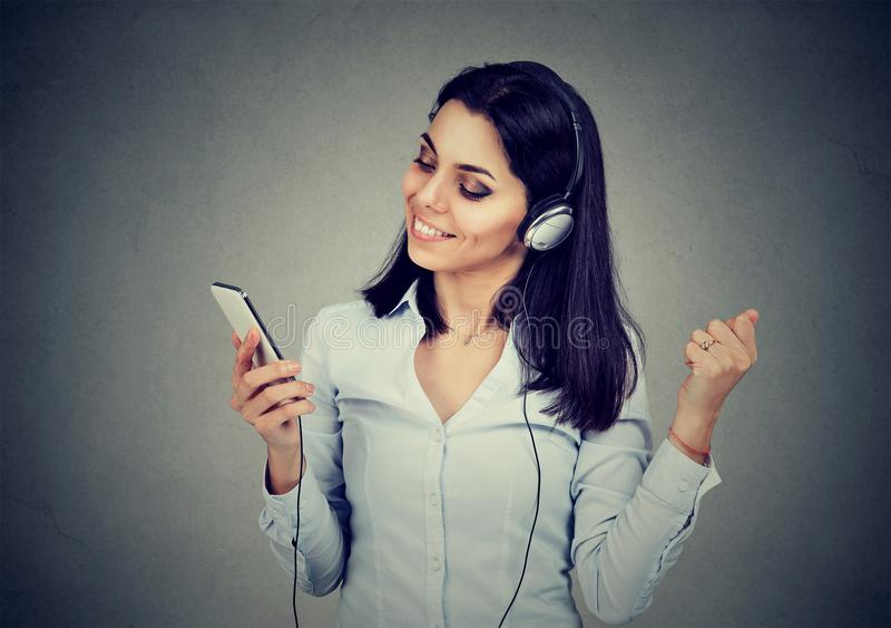 Giovane donna di dancing che ascolta la musica in cuffie e che tiene telefono cellulare su fondo grigio scuro fotografie stock libere da diritti