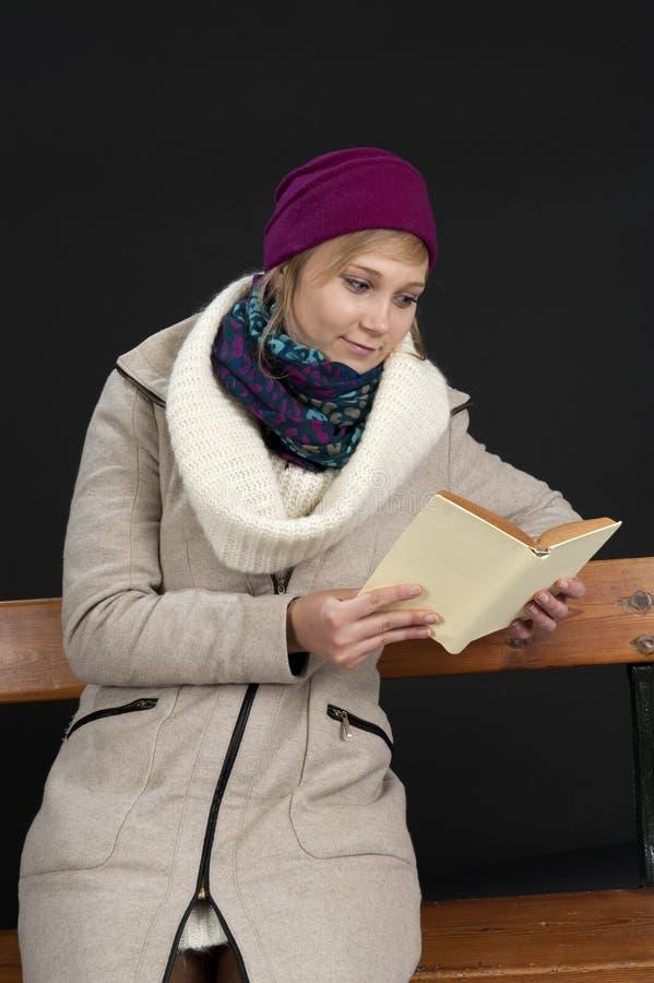 Giovane donna di Eading in vestiti di inverno sul nero fotografie stock